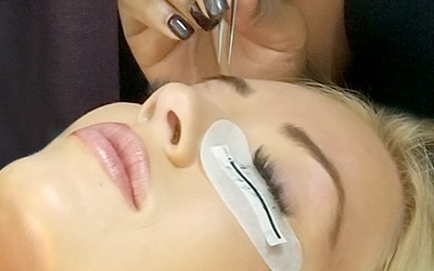 Lash Stylist applies Amazing Volume Classic (3D) lash extensions to a guest's eyelashes