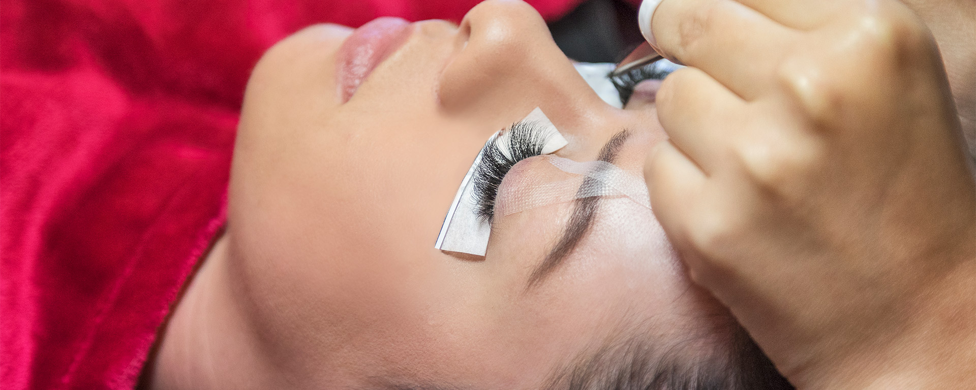 Guest relaxes with eyes closed while stylist applies eyelash extensions